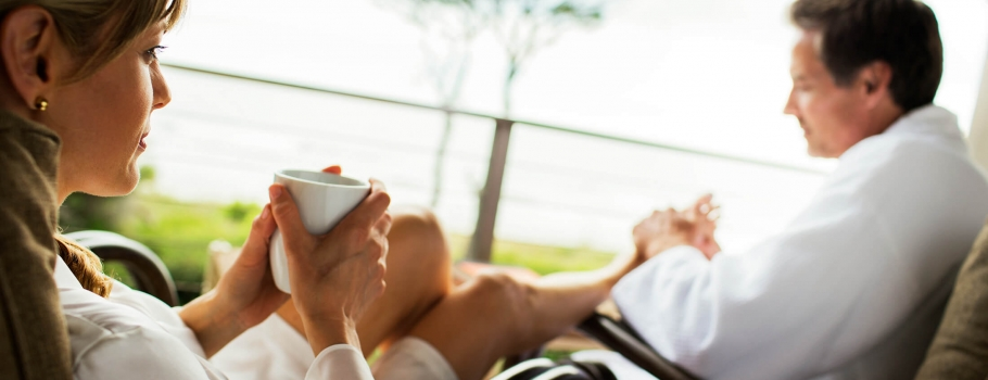 woman enjoying a hot beverage and a foot massage