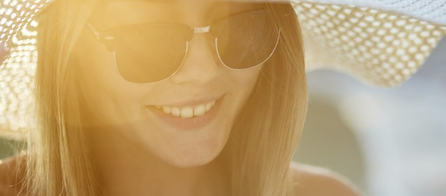 Smiling girl wearing wide brim straw hat and sunglasses