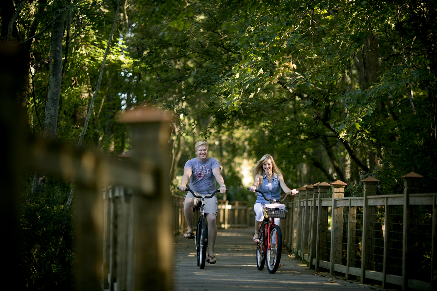 couple riding bikes on wooden path through woods