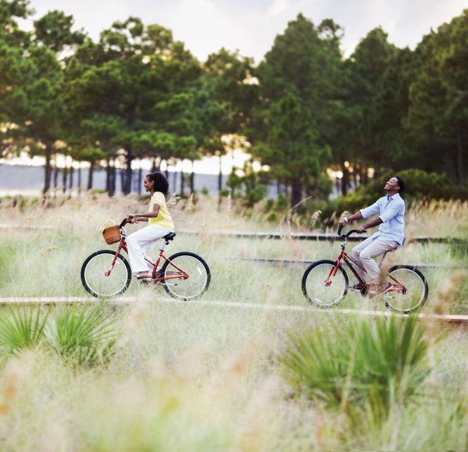 Couple riding bicycles along the boardwalk