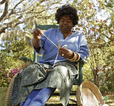 A Gullah woman weaving sweetgrass baskets