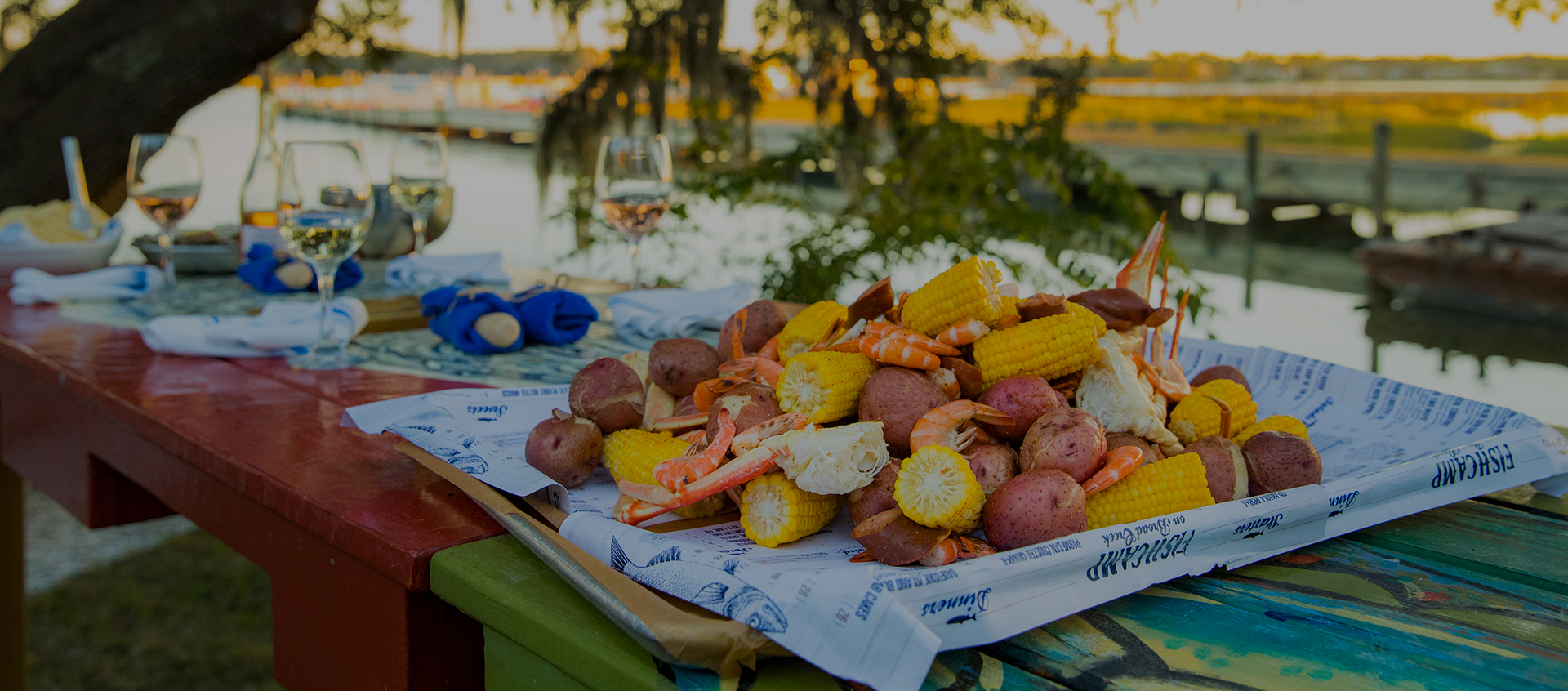 picnic table full of potatoes, corn, and seafood