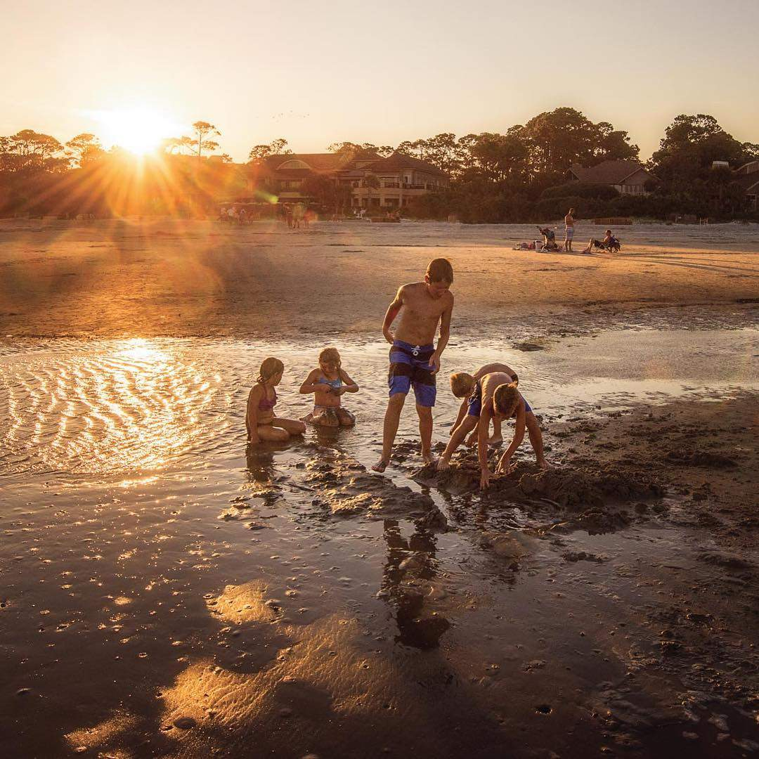 Family building a sandcastle at sunset on Hilton Head Island