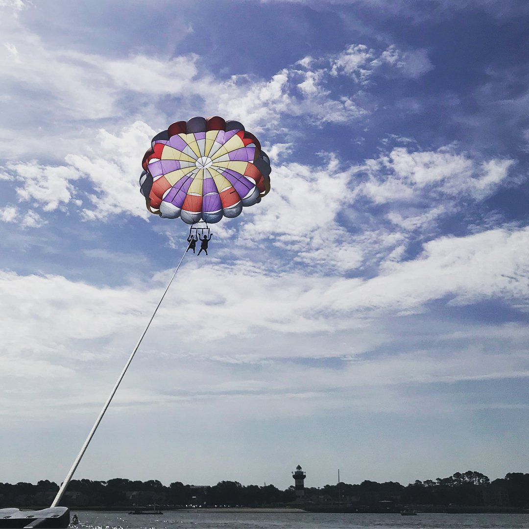 Couple parasailing over Hilton Head Island with purple parachute