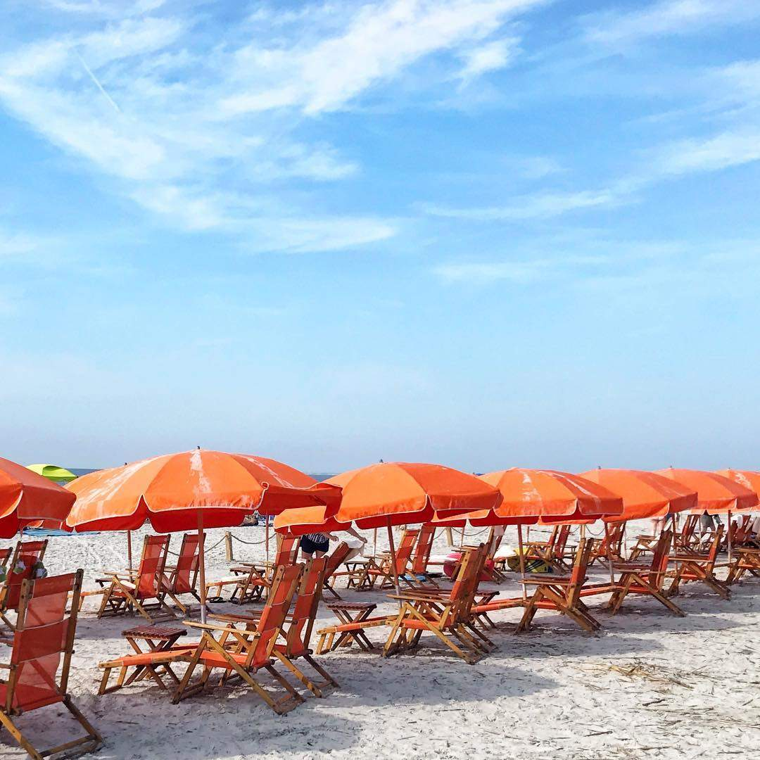 Orange beach umbrellas lining the coast of the Sea Pines Beach Club