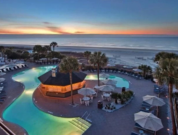 Bird's eye view of the Beach House Resort pool area at sunset