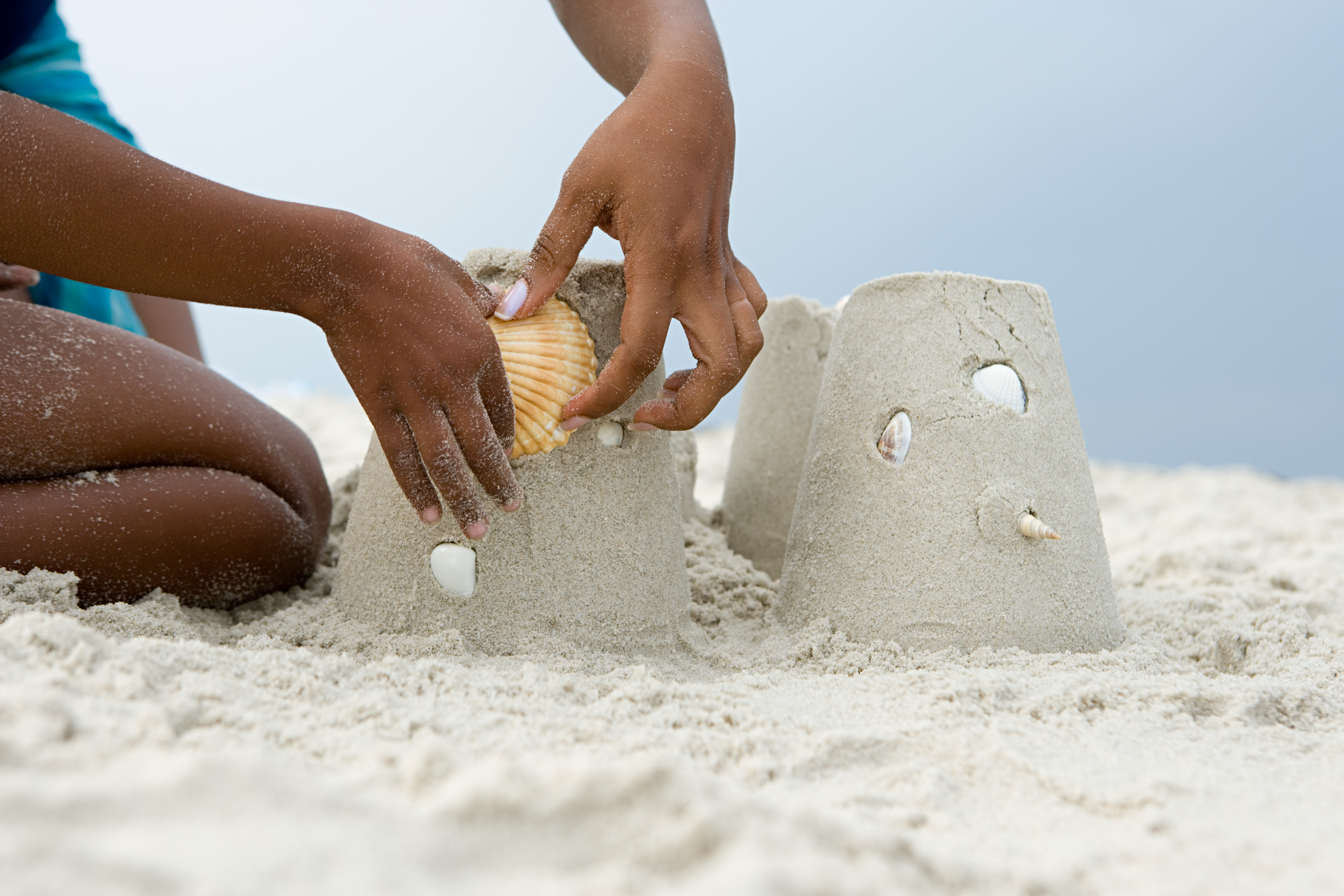 Hand placing shell on sand castle