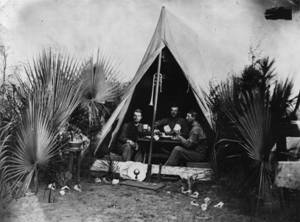 Black and white photo of people in tent