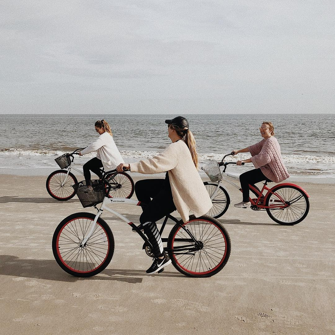 Group of friends riding bikes on the beach.