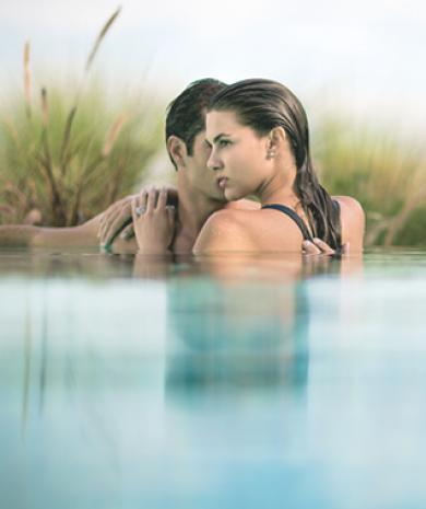 Couple embracing in pool.