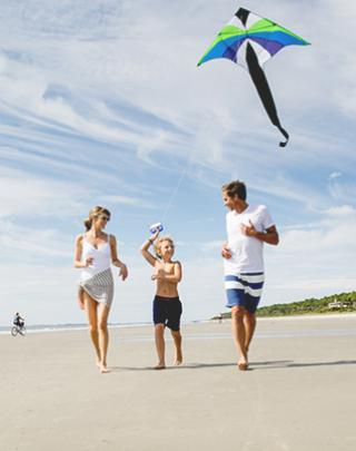 Family flying a kite on the beach.
