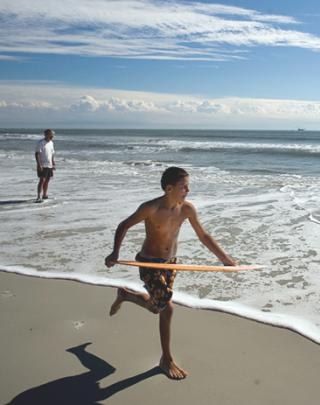 Boy running on the beach with a hula hoop.
