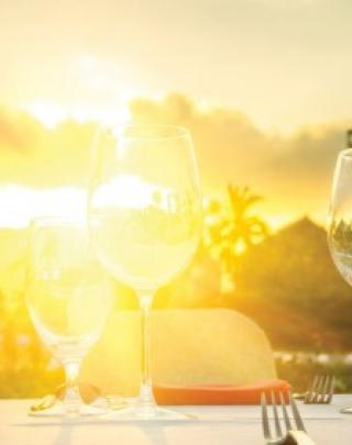 Wine glasses on table with sunset in background
