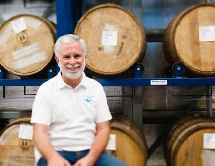 man sitting in front of wine barrels