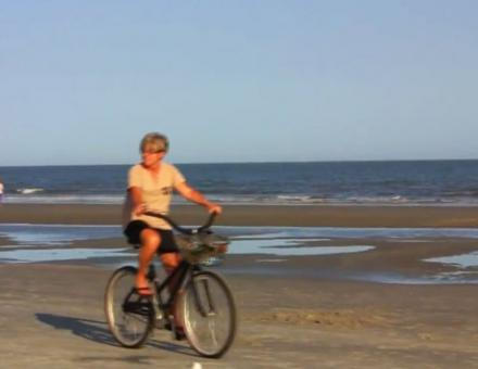 A woman biking on the beach