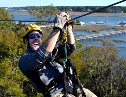 A man, smiling, about to zipline