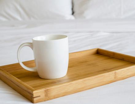 A coffee cup on a tray in bed