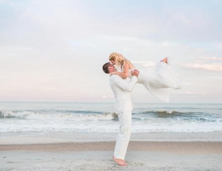 A bride and groom on a white sandy beach