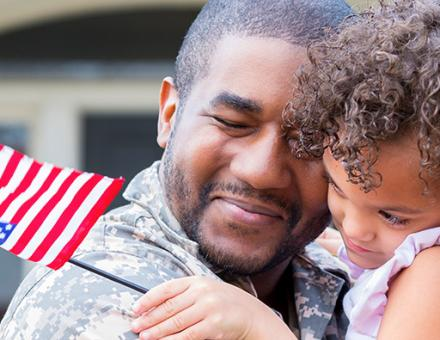 Military father hugging child.