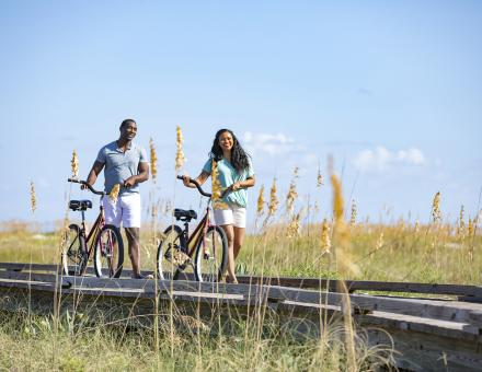 A couple walking their bikes along a boardwalk on a sunny day in Hilton Head Island