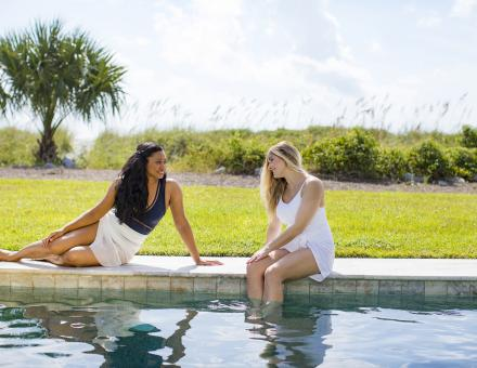 Two women sitting by a hotel pool in white dresses in Hilton Head Island