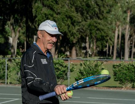 Tennis pro Stan Smith balances a tennis ball on a tennis racket.