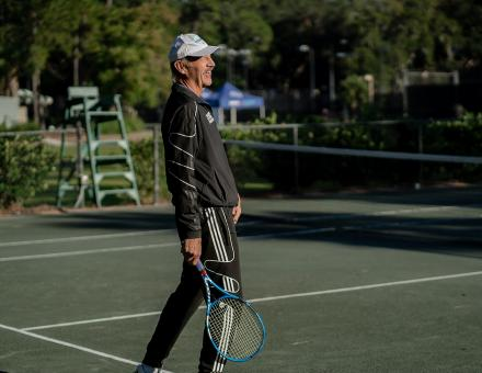 Tennis pro Stan Smith laughs on a tennis court holding a tennis racket.