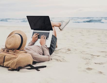Person working on laptop on the beach