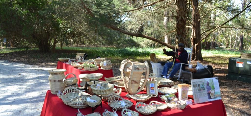Tabe with red cloth showcasing Gullah woven baskets