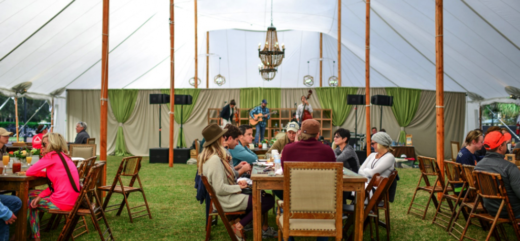 Group of people surrounded by table under a gazebo