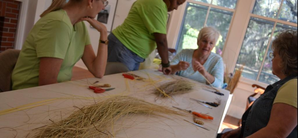Table of sweetgrass, bulrush, pin needles, and women doing arts and crafts