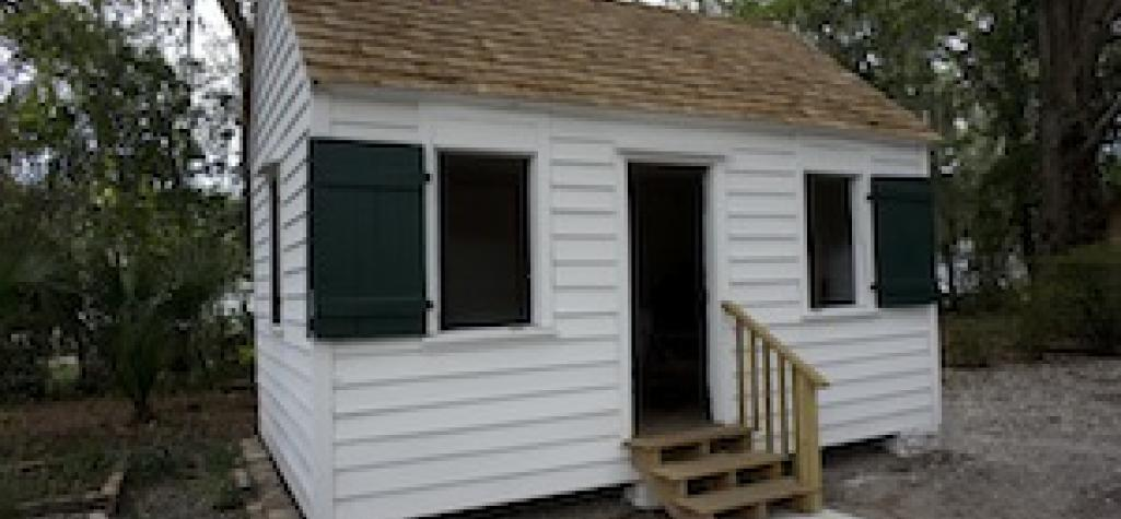 Small white shed with shingled roof