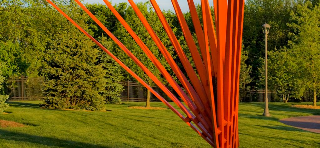 Abstract piece of orange art displayed in front of green trees and grass.