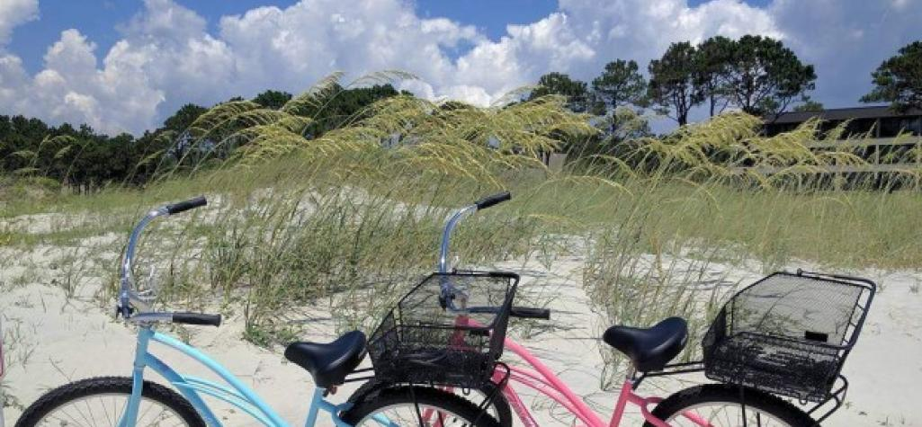 A blue bike and a pink bike on the beach