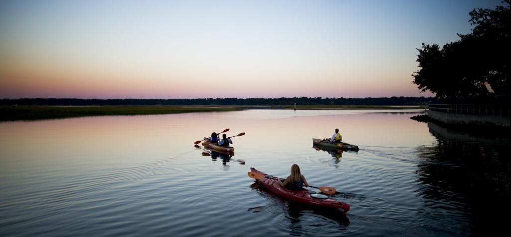 Three kayakers at dawn