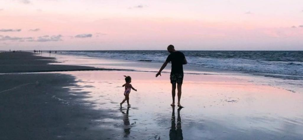 Father and daughter walk along the beach at sunset