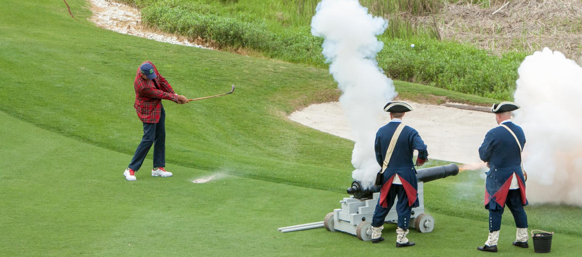 man hitting wedge while canons go off
