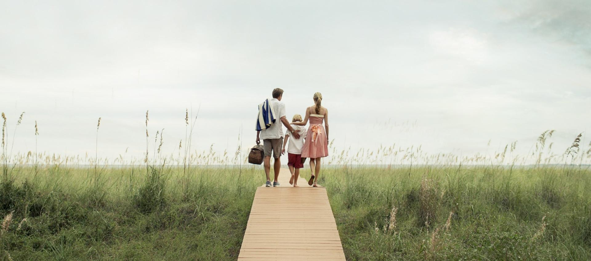 A family walking on the boardwalk towards the beach