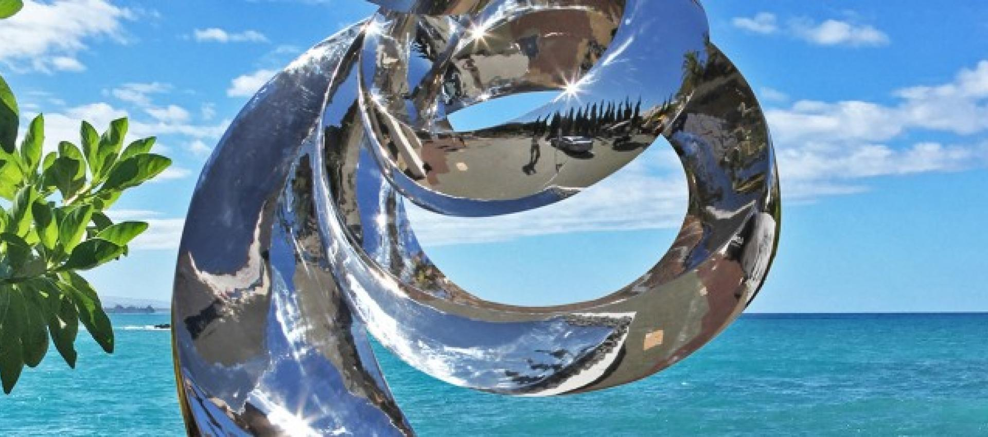 Silver art pice in front of bright blue water and sky.