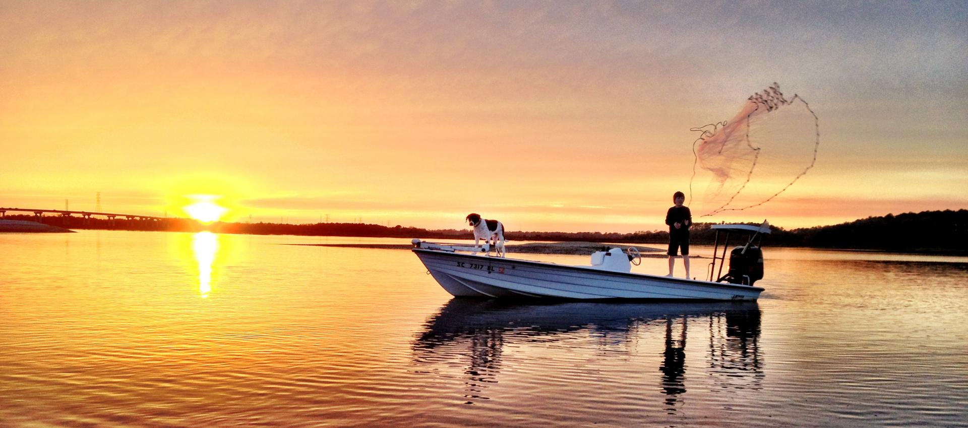Man fishing at sunset with a dog on Hilton Head Island
