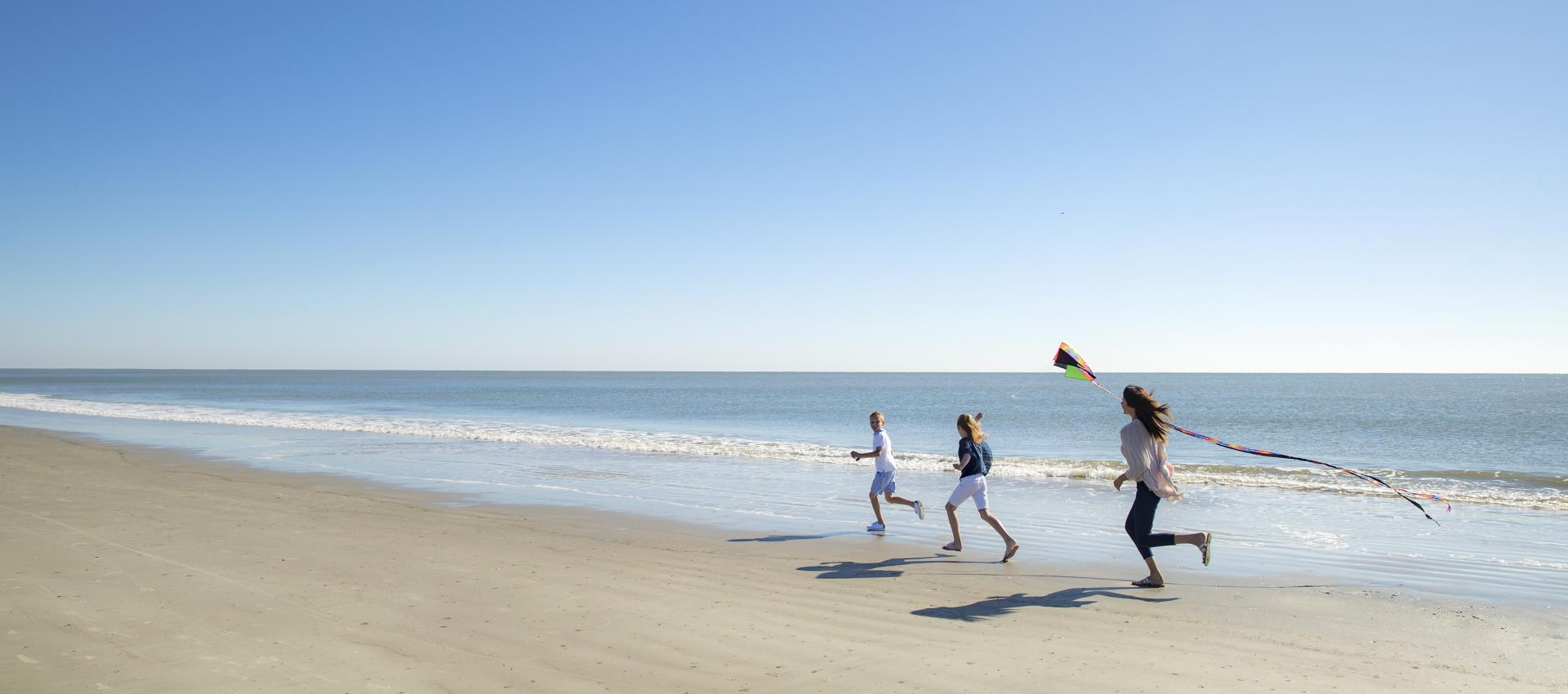 Family flying kite on beach.
