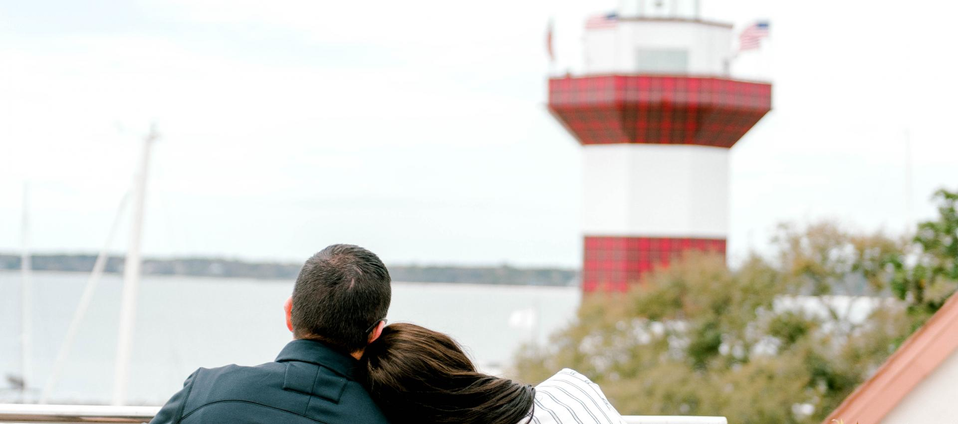 Couple sits facing the Harbour Town Lighthouse