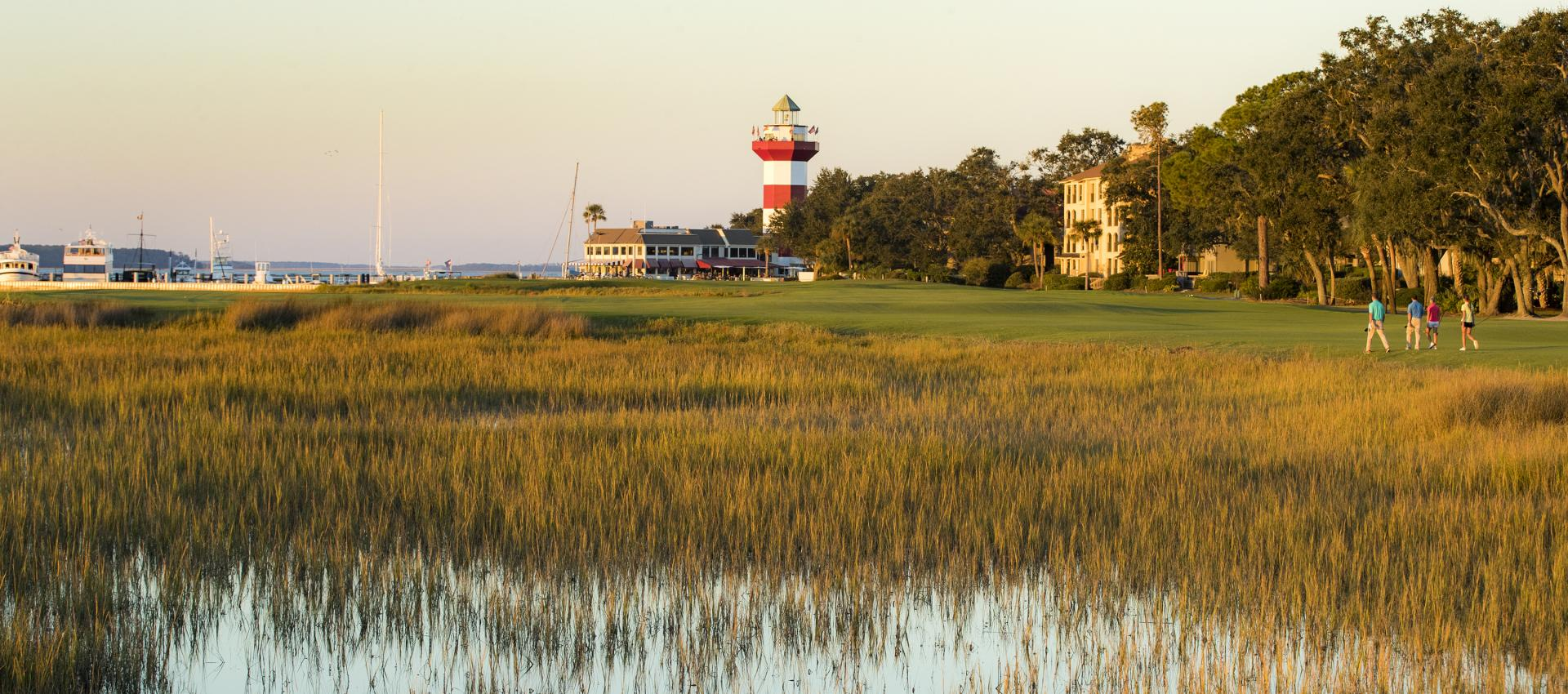 A wide angle shot of the 18th green of Harbour Town Golf Links. In the distance is the lighthouse, sunset, and 4 golfers in the distance.