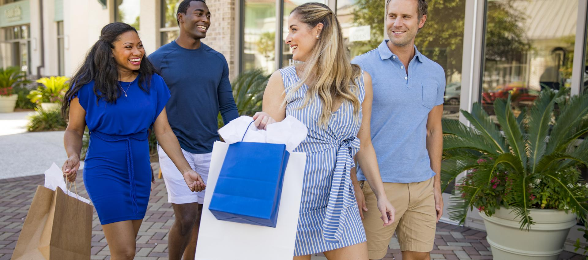 Two men and two women shop with large shopping bags