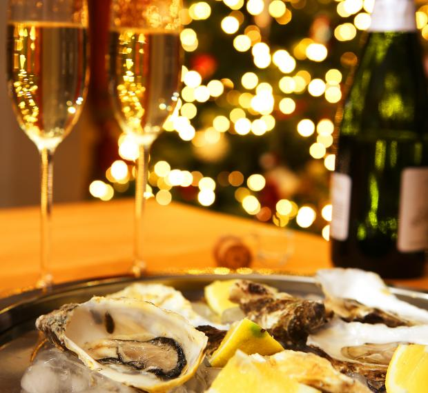 oysters and champagne in front of christmas tree
