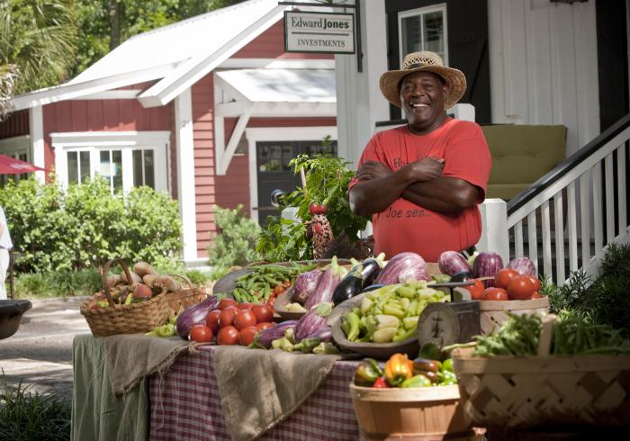 A man smiling behind is fruit stall at the Bluffton farmers market.