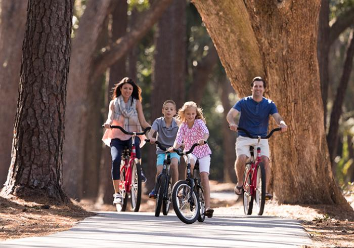 Family biking through the trees