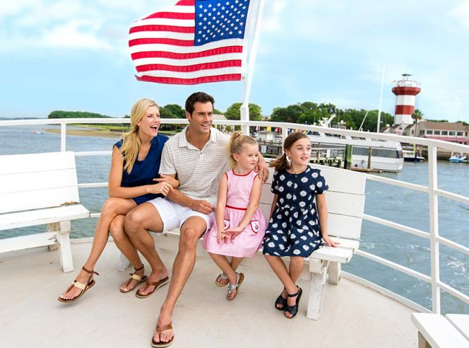 Family sitting on a boat in front of the American flag