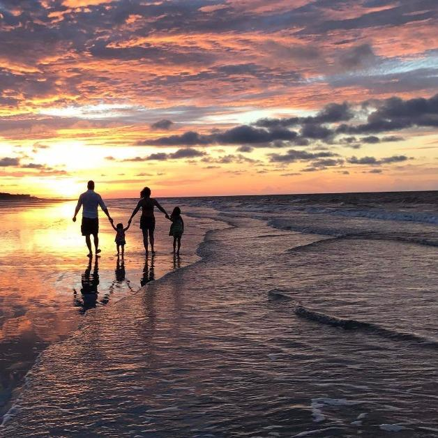 family walking on beach into sunset
