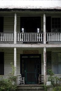 Front of abandoned house with two chairs on front porch
